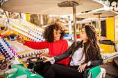 istock Two friends riding amusement park ride 1134781026