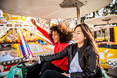 istock Two friends riding amusement park ride 1134934659