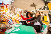 istock Two friends riding amusement park ride 1135779881