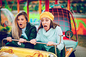 istock Two friends riding amusement park ride 1136444377