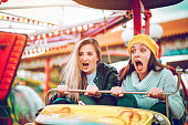 istock Two friends riding amusement park ride 1136444616