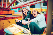 istock Two friends riding amusement park ride 1136444639