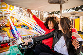 istock Two friends riding amusement park ride 1136804506
