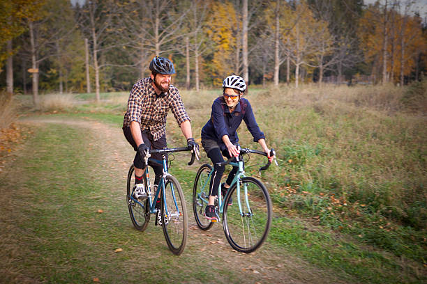 Two friends riding their bicycles through the woods stock photo
