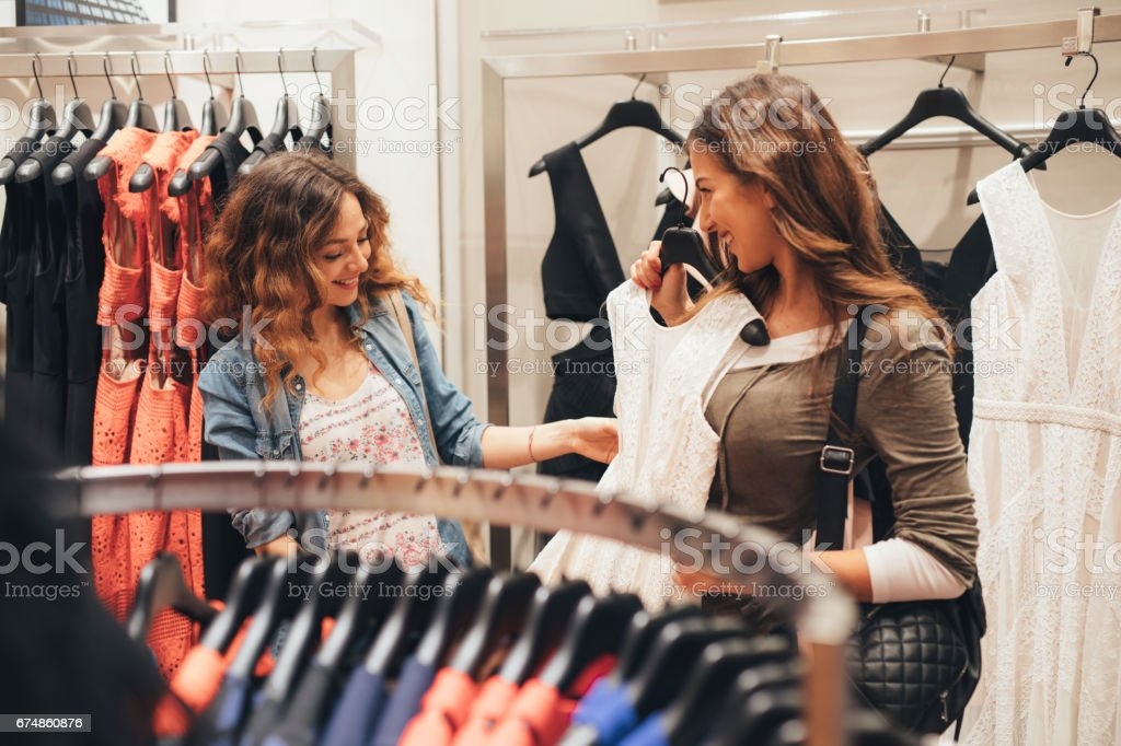Two friends shopping for clothes stock photo