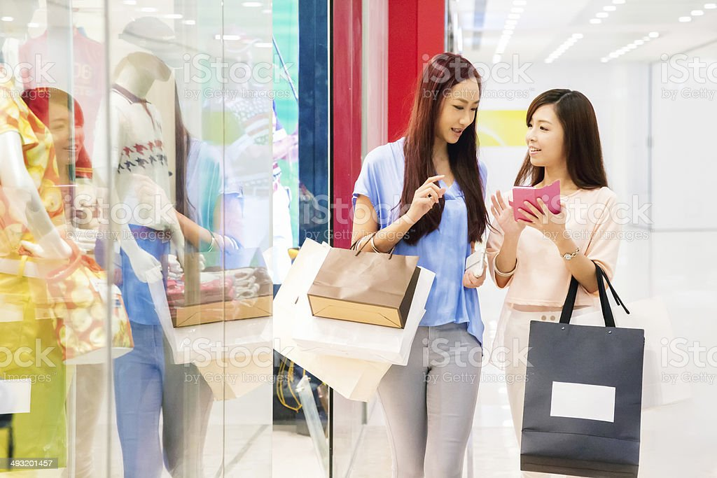 Two friends shopping with mobile phone stock photo