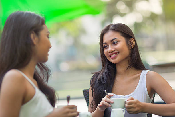 two friends sitting at a cafe together - philippines girl stock photos and pictures