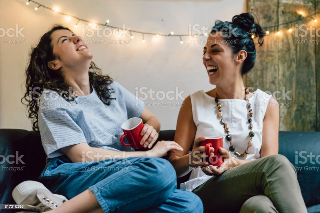 Two friends sitting on a sofa drinking coffee together stock photo