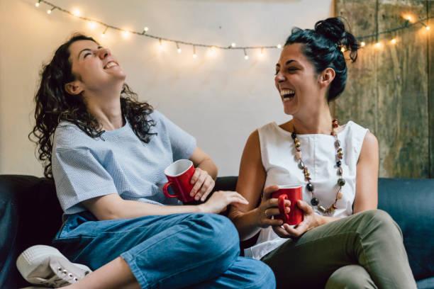 dos amigos sentados en un sofá tomando café juntos - happy couple sharing a cup of coffee fotografías e imágenes de stock