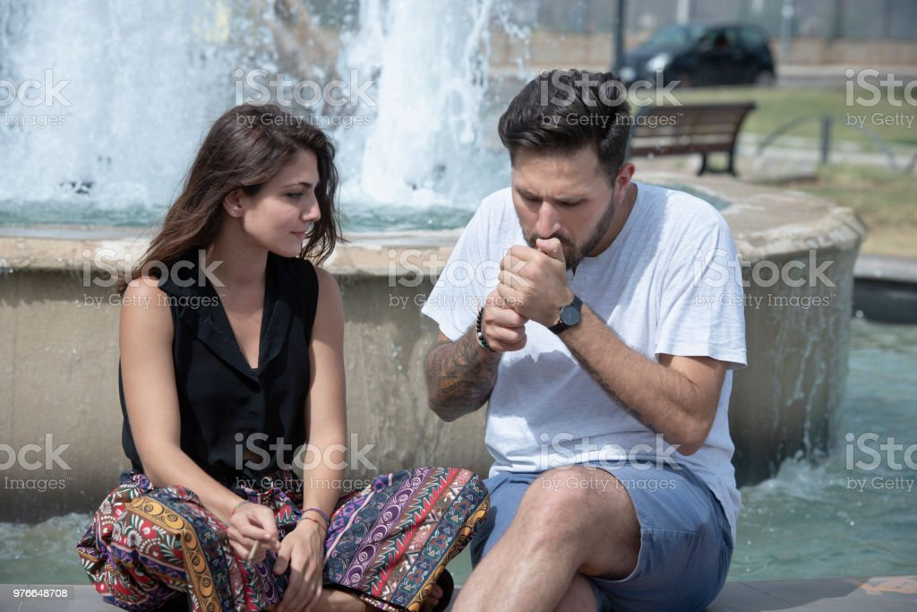 Two friends smoking in the public park - foto stock