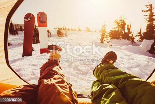 Two friends snowboarders are relaxing in tent against sunset. Ski resort concept