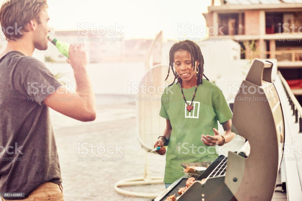 Two friends socialising together whilst cooking meat on a barbecue royalty-free stock photo