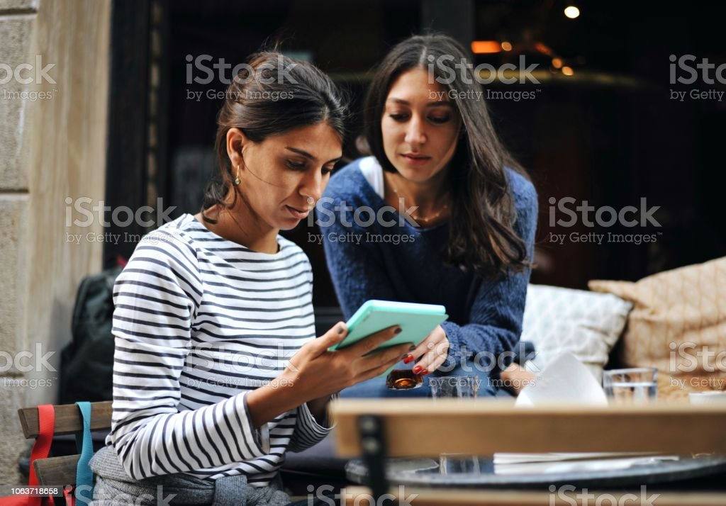 Two friends spending time with a digital tablet at a cafe stock photo