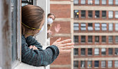 Two downtown apartment neighbors waving to each other during shelter-in-place orders due to the Coronavirus pandemic of 2020.