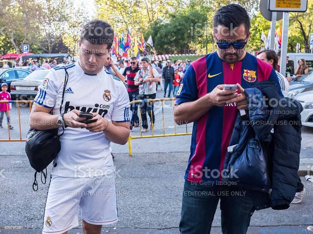 Dos amigos apoyar Real Madrid con Barcelona mientras ve sus Smartphones - foto de stock