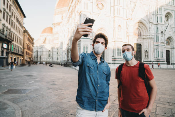 Two friends taking a selfie together with face masks in Florence, Italy stock photo