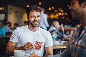 istock Two Friends Talking in a Cafe 613518378