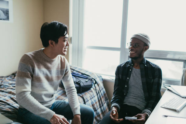 two friends talking in a dorm room - two students together asian foto e immagini stock