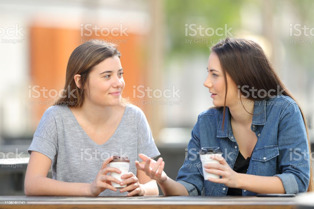 Two friends talking in a park drinking coffee royalty-free stock photo
