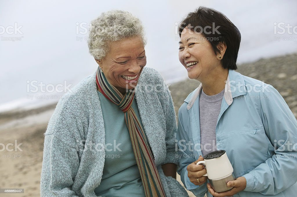 Two Friends Talking over Coffee on the Beach stock photo