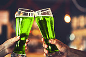 istock Two friends toasting with glasses of green beer at the pub with free space for your text. Beautiful background of the Oktoberfest and St. Patrick's day. fine grain. Soft focus. Shallow DOF 645060850