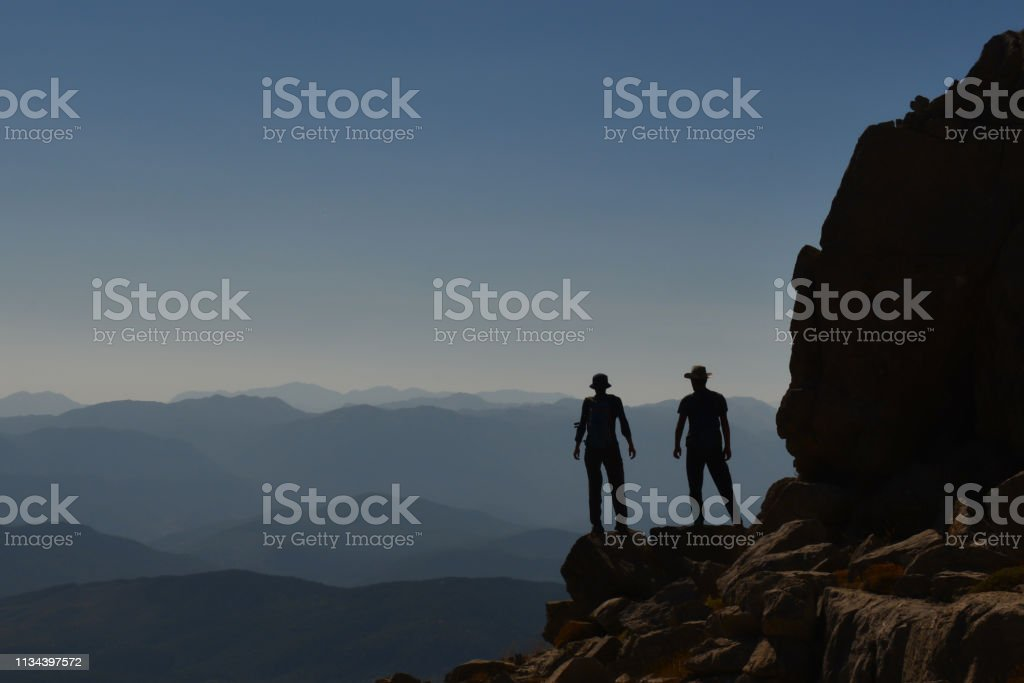 two friends triumph in the magnificent mountains stock photo