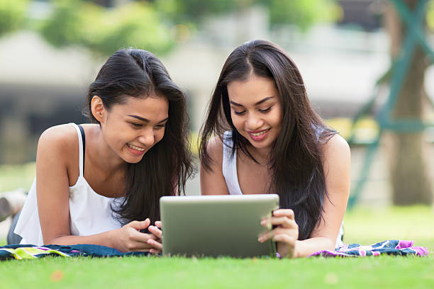 two friends using a tablet computer - philippines girl stock photos and pictures