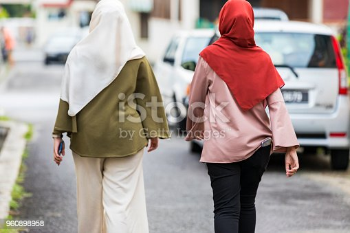 Rear view of two women wearing hijabs walking home after a day together in the city.