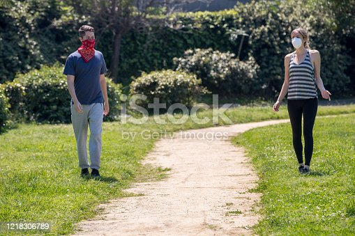 Two friends walking in a park keeping social distance while wearing face masks during the Coronavirus pandemic.