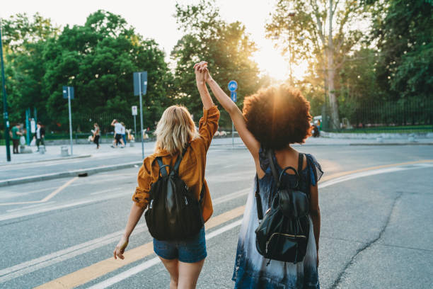 Two friends walking together in the city at sunset stock photo