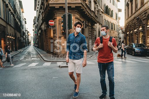 Two friends walking together in the city wearing protective face masks. They are wearing the masks due to the coronavirus Covid-19 pandemic.