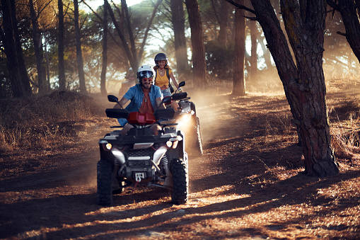 Two young friends wearing helmets having fun and riding quad bikes together in the forest