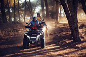 istock Two friends wearing helmets having fun and riding quad bikes together in the forest 1271144424