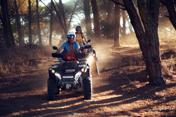 Two friends wearing helmets having fun and riding quad bikes together in the forest stock photo