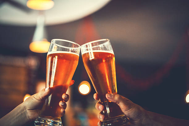 two friends with glasses of beer. shallow dof - happy hour stock photos and pictures