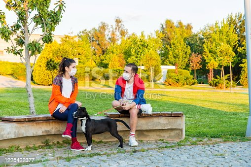 Two friends are sitting down while talking in the park