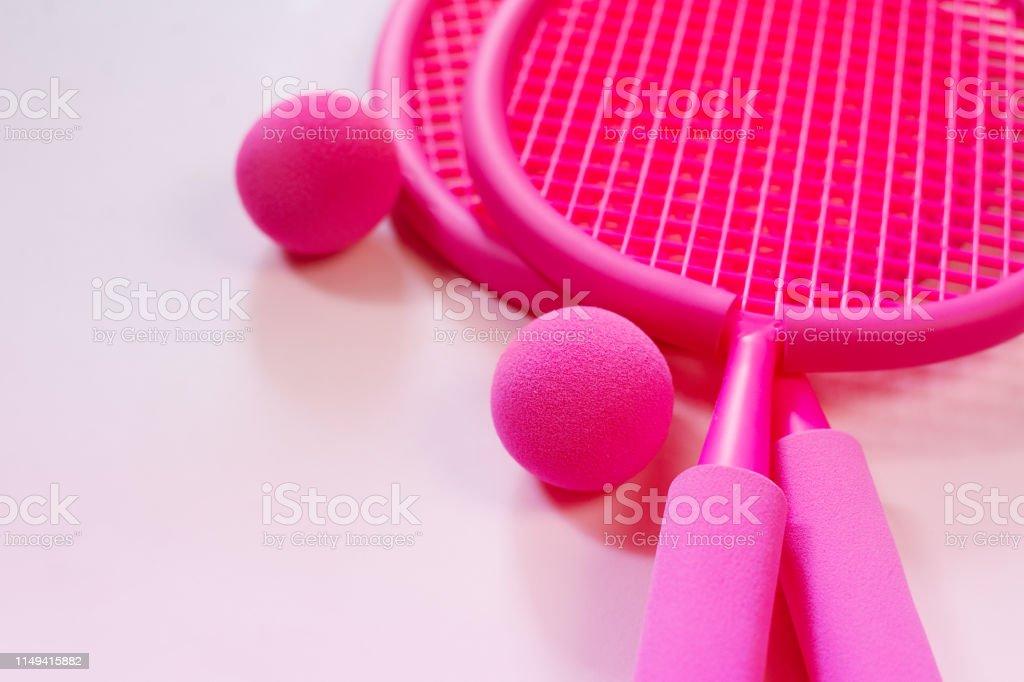 Two fuchsia pink beach tennis rackets and ball top view summer fun