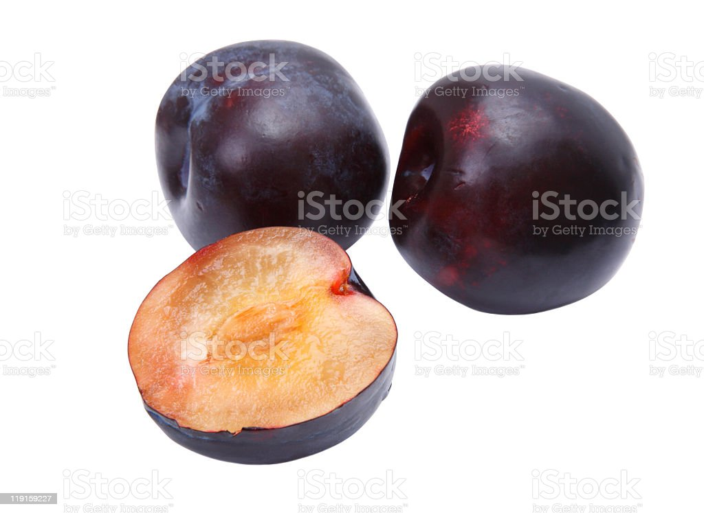 Two full and one half black plum on a white surface royalty-free stock photo