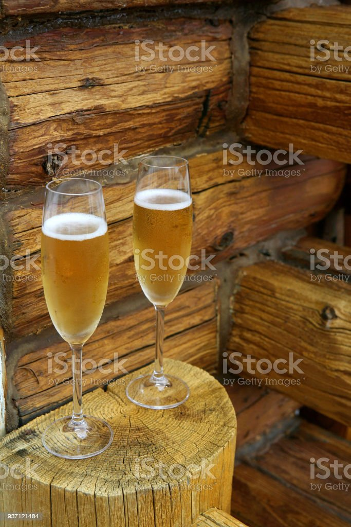 two full Champagne glass in front of a log home wall stock photo