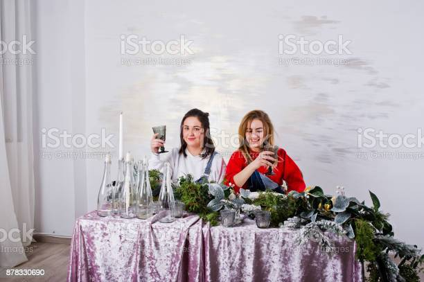 Two fun beautiful girls friends wear in overalls jeans shorts and gaiters against table with new year decoration.