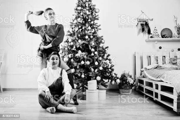 Two fun beautiful girls friends wear in overalls jeans shorts and gaiters against new year tree with chrisrmas decoration.
