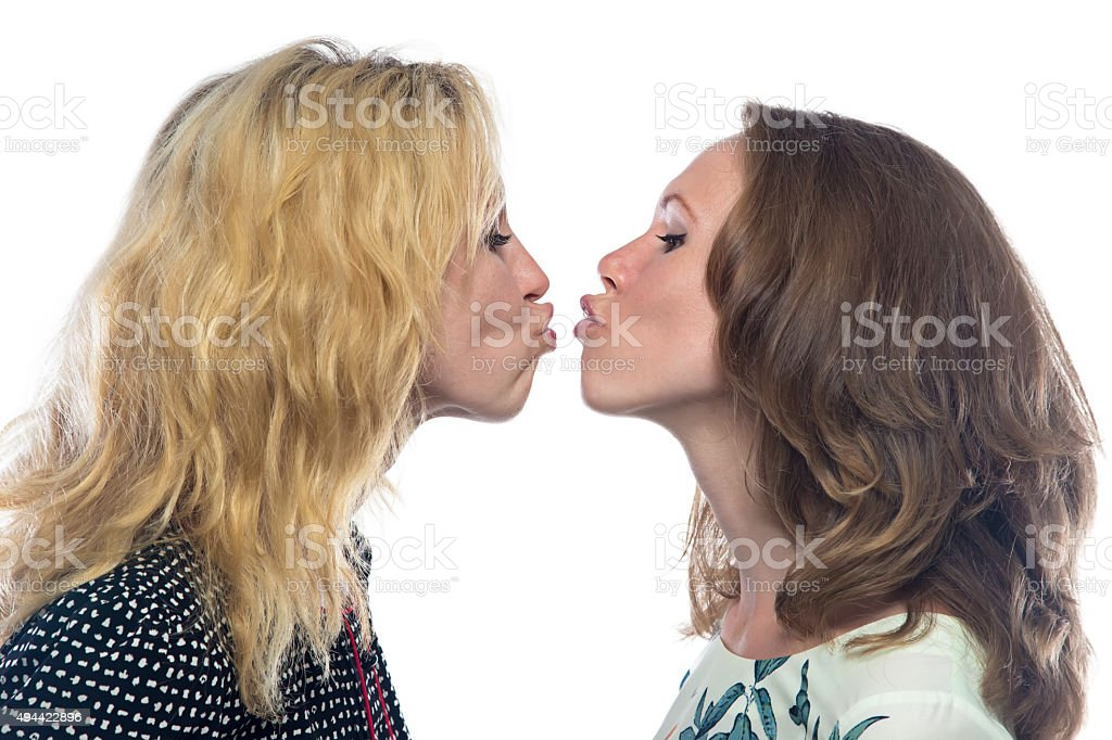 Two fun kissing sisters stock photo