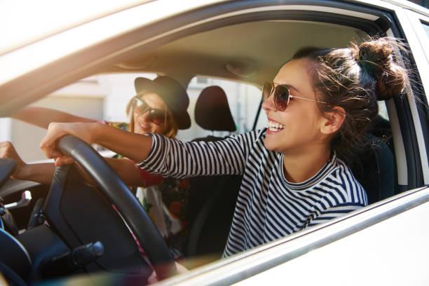 Two fun young women driving in a car stock photo