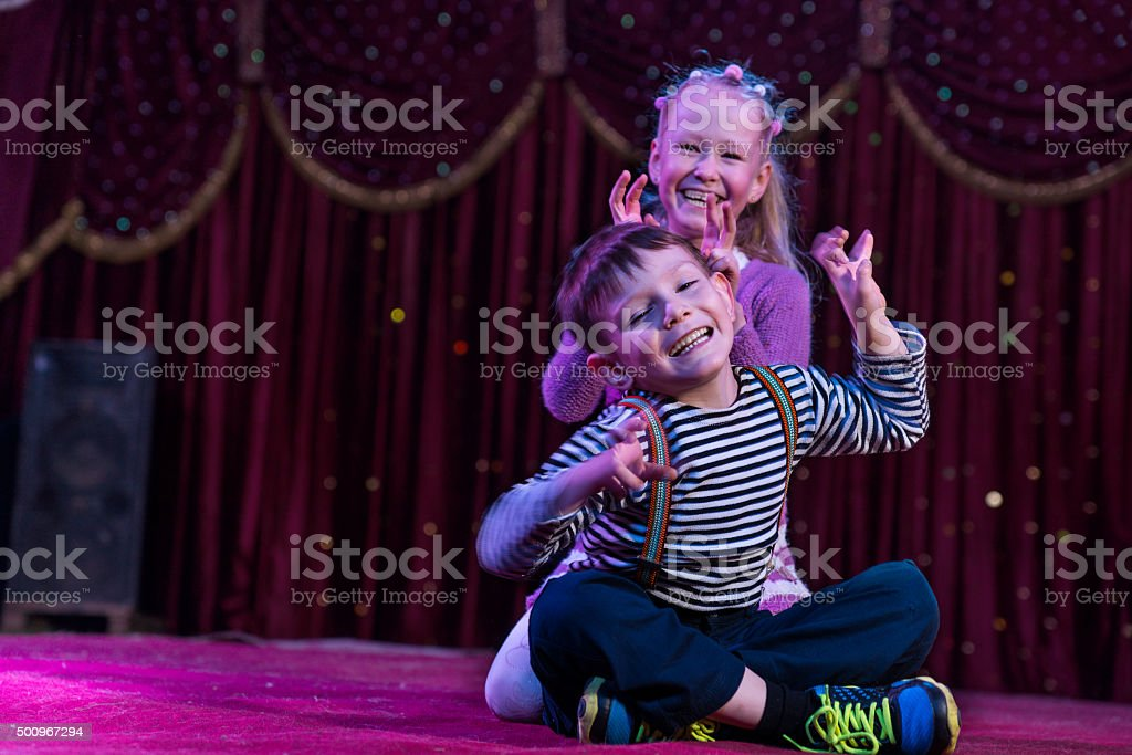 Two funny children acting as monsters on stage stock photo
