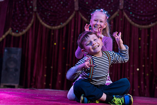Two funny children acting as monsters on stage Two funny playful children, boy and girl, smiling while acting as monsters with claws, on a purple stage, in a theatrical representation theatrical performance stock pictures, royalty-free photos & images