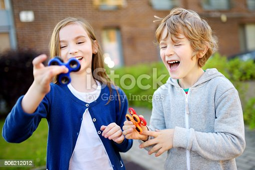 istock Two funny friends playing with fidget spinners on the playground. Popular stress-relieving toy for school kids and adults. 806212012