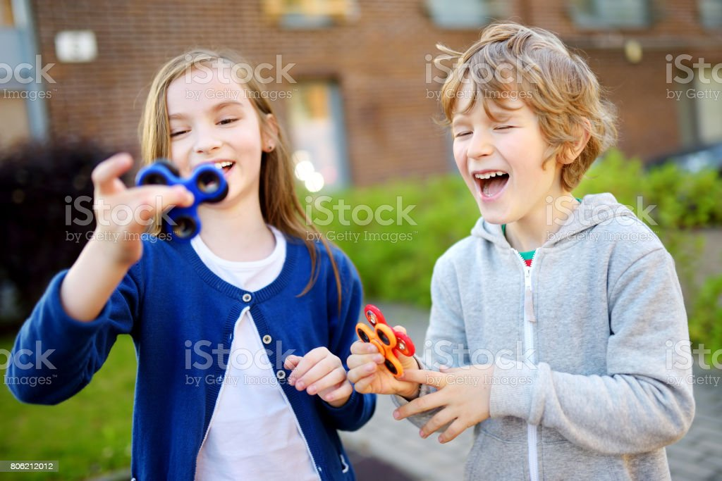 Two funny friends playing with fidget spinners on the playground. Popular stress-relieving toy for school kids and adults. stock photo