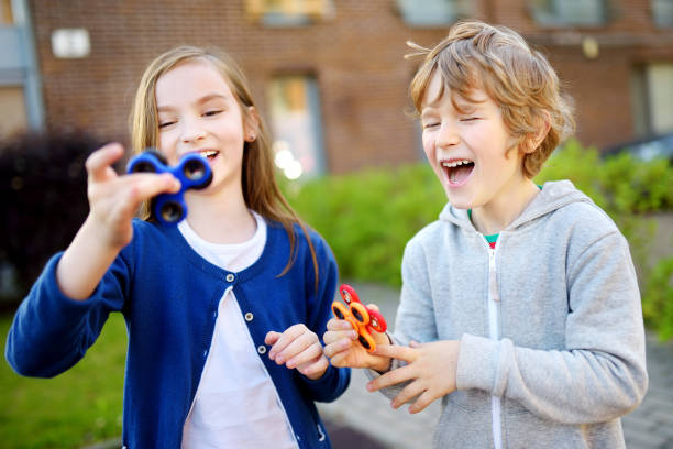 two funny friends playing with fidget spinners on the playground. popular stress-relieving toy for school kids and adults. - autism stock photos and pictures