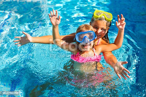 Two funny girls playing in swimming pool. Vacation and travel concept