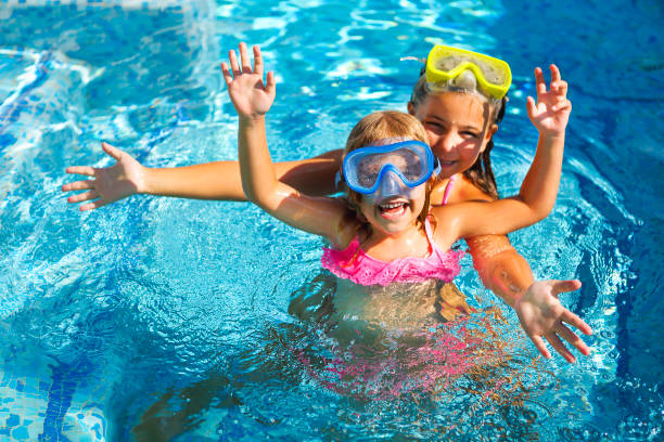 Two funny girls playing in swimming pool stock photo